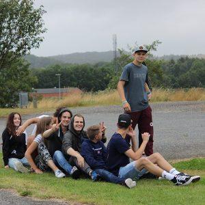 Jugendliche sitzen hintereinander auf dem Boden