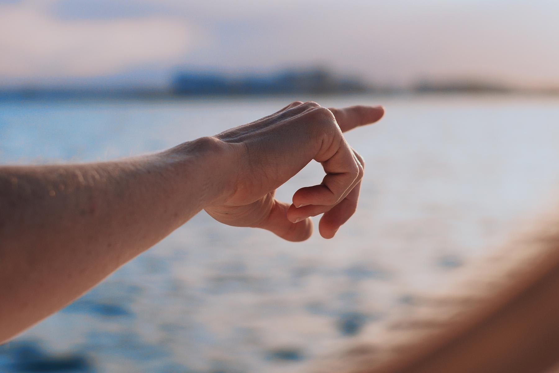 Hand zeigt am Meer Richtung Horizont