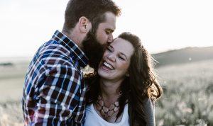 Mann küsst Frau auf die Schläfe