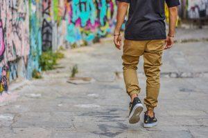Mann geht auf Strasse links sind Grafities zu sehen