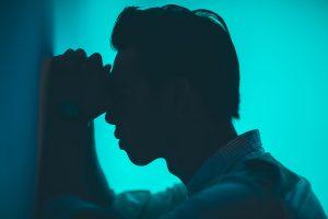 Verzweifelter Mann lehnt Hände und Kopf an Wand
