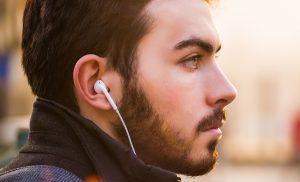 Mann mit Kopfhörern im Ohr hört die Hörbibel