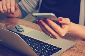 Frau hält Smartphone in der Hand über einem Laptop