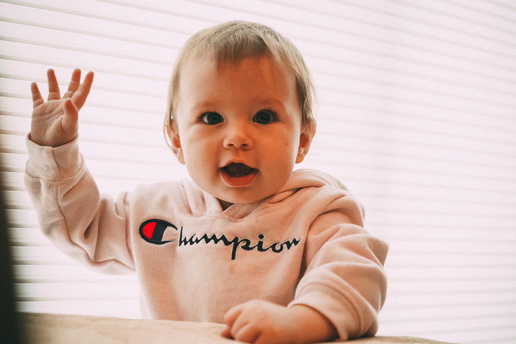 Kleines Kind mit Champions Pulover hebt rechte Hand