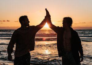 Zwei Männer klatschen ab beim Sonnenuntergang am Meer