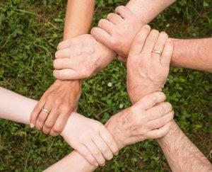 Mehrere Hände greifen sich gegenseitig am Handgelenk und bilden so einen Kreis aus Armen
