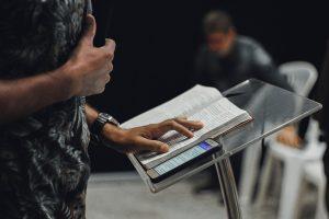 Prediger mit Hand auf der Bibel und Smartphone