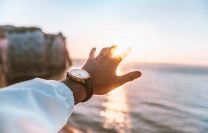 Hand streckt sich nach dem Horziont aus über dem Meer