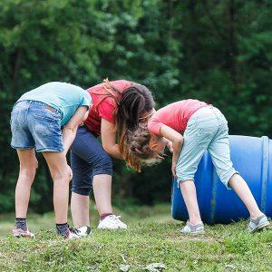 Kinder schauen in ein Fass