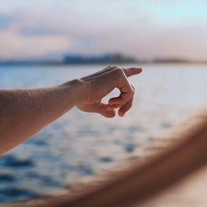 Eine Hand zeigt auf etwas am Horizont