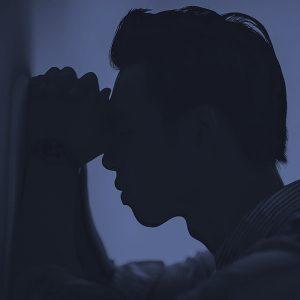 Verzweifelter Mann lehnt mit Kopf an einer Wand