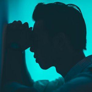 Mann lehnt mit Kopf an einer Wand und wirkt verzweifelt