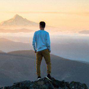 Mann auf einem Gipfel schaut sich die Berge an