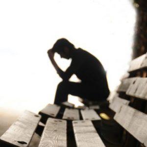 Mann sitzt auf einer Bank und wirkt verzweifelt